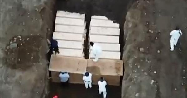 Watch: Workers bury corpses in a mass grave on Hart Island, New York