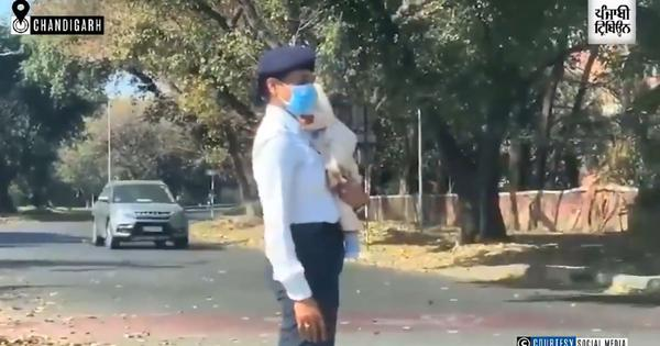 Watch: Police constable regulates traffic with a baby in her arms