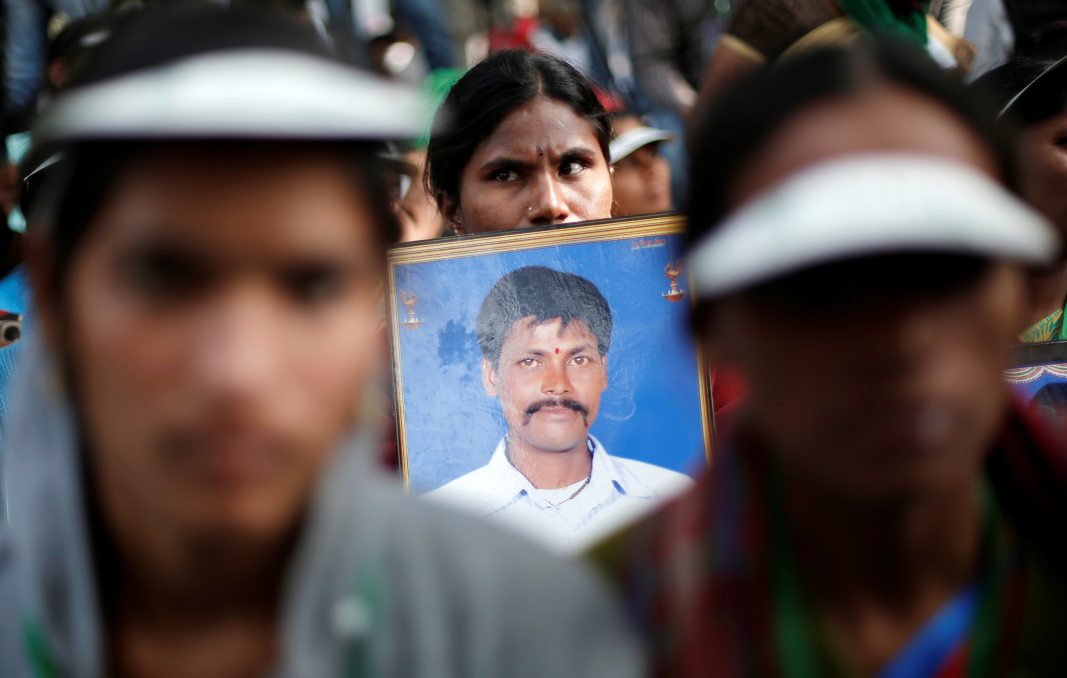 A farmer from Telangana holds a picture of her husband, who, she says, committed suicide, during a protest in Delhi. Photo credit: Reuters