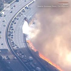 Watch: Aerial footage shows helicopters containing a brush fire on a California freeway