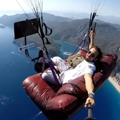 Watch: Paragliding instructor flies off a cliff while sitting on a sofa and watching TV