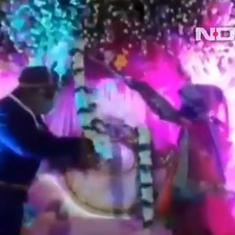 Watch: At a physically distanced wedding, bride and groom garland each other using bamboo sticks